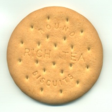 Close up view of a single Round Rich Tea Biscuit showing the texture and text on a white background